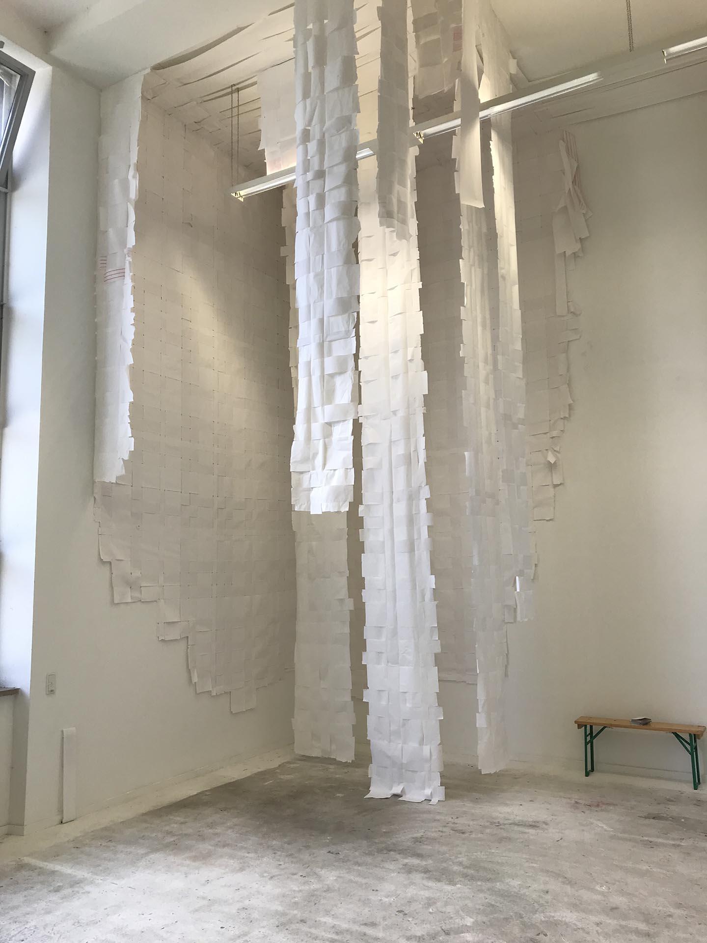 Abbildung Carte Blanche Installation. Von der Decke hängende Papierbahnen